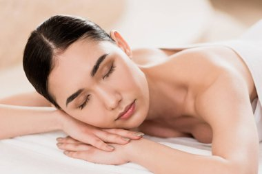 beautiful asian woman resting with closed eyes at spa