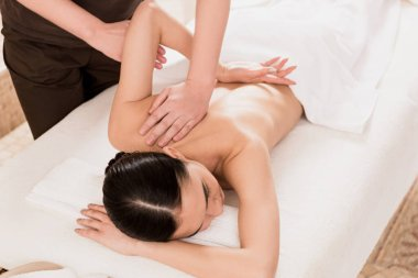 partial view of masseur doing back massage to beautiful woman