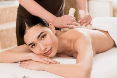 selective focus of woman getting back massage and looking at camera