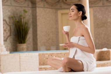 attractive asian woman in towel drinking coffee at spa