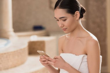 attractive asian woman in towel using smartphone at spa