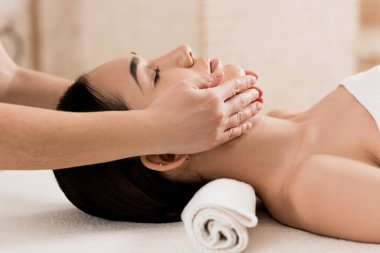 beautiful woman getting face massage with closed eyes at spa