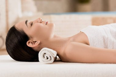 side view of asian woman lying and relaxing at spa