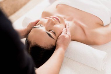 beautiful asian woman getting face massage with closed eyes at spa