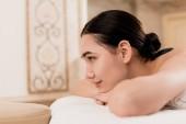 Fotografia Profilo di bella donna asiatica che si trova sul lettino da massaggio e relax al centro benessere
