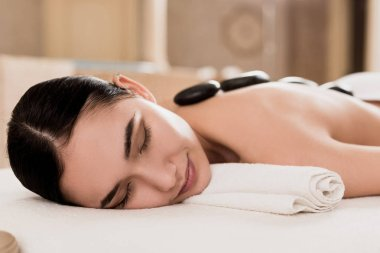 selective focus of attractive woman getting stone massage at spa