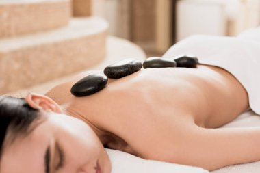 cropped view of woman getting stone massage at spa