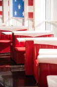 Photo interior of cafe with red sofas and white tables