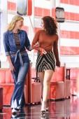 Fotografia belle donne a piedi, tenendosi per mano, guardando laltro e sorride alla caffetteria