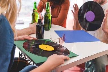 selective focus of friends holding vinyl and glass bottles with drink