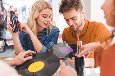 selective focus of handsome and beautiful friends talking, holding vinyl and glass bottles with drink