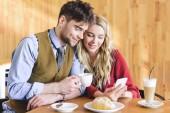 pohledný muž, který držel šálek kávy a žena pomocí smartphone v kavárně