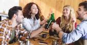 Fotografie hübsch und schöne Freunde lachen und jubeln mit Glasflaschen im café