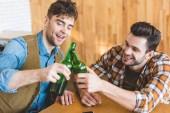 gut aussehend und lächelnde Männer jubeln mit Glasflaschen Bier
