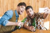 jóképű férfiak üveg sört és figyelembe selfie kávézóban