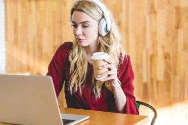 attractive woman with headphones holding paper cup and using laptop