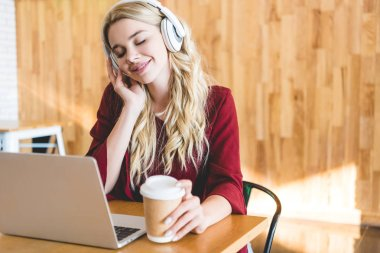 selective focus of beautiful woman listening music with headphones and holding paper cup