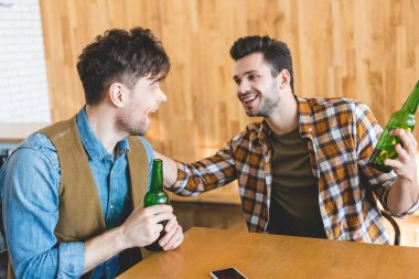 Handsome and smiling men holding glass bottles of beer and talking stock vector