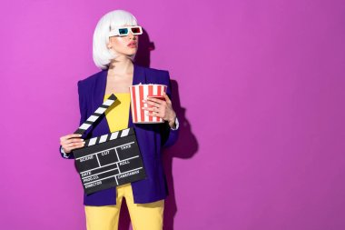 Interested girl in 3d glasses holding clapperboard and popcorn and looking away on purple background