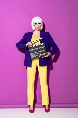 Stylish young woman in 3d glasses holding clapperboard on purple background stock vector