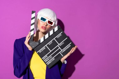 Girl in white wig and 3d glasses holding clapperboard on purple background