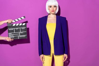 Confident girl in blue jacket and white wig standing on purple background
