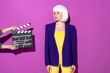 Sensual girl in white wig looking at clapperboard on purple background stock vector