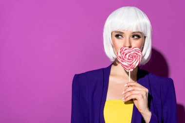 Stunning girl in white wig eating heart-shaped lollipop on purple background stock vector