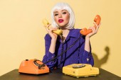 Okouzlující žena v modrá halenka držení mobilních telefonů na žlutém podkladu