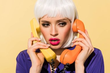Amazed woman in white wig holding handsets isolated on yellow stock vector