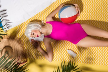 Top view of girl in wig and pink swimsuit with ball lying on yellow towel