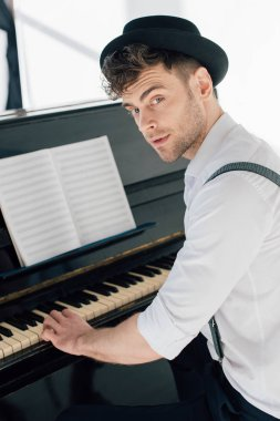 handsome pianist in stylish clothing playing piano at home