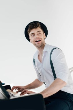 cheerful pianist in white shirt and black hat playing piano