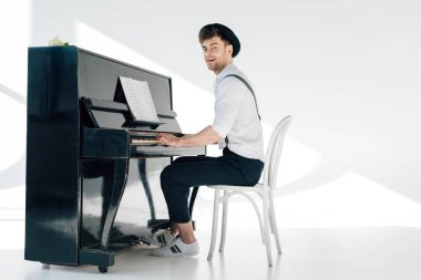smiling pianist in trendy clothing playing piano