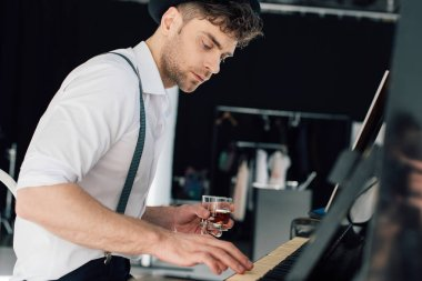 selective focus of handsome pianist playing piano and holding glass of alcohol drink