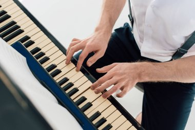selective focus of pianist in white shirt playing piano