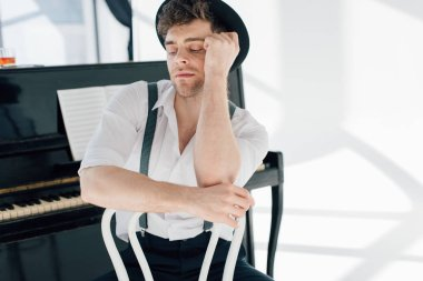 handsome dreamy pianist in white shirt and black hat sitting on white chair