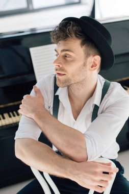 selective focus of dreamy composer in white shirt and black hat