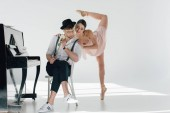 Fotografie handsome musician sitting on chair with rose while young ballerina dancing near him