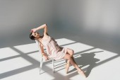beautiful young ballerina sitting on white chair in sunlight