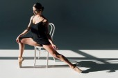 attractive young ballerina in black dress stretching on white chair