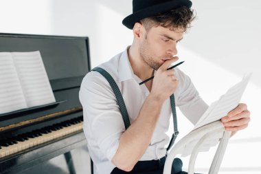 selective focus of thoughtful musician holding music book sheets