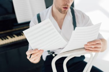 selective focus of man holding music book sheets