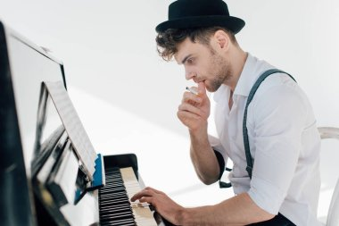 thoughtful musician composing music while sitting at piano