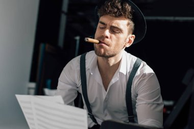 handsome musician holding music book sheets while smoking cigar