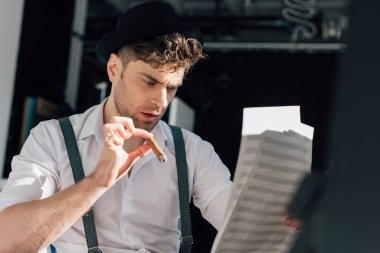 selective focus of handsome musician with cigar, reading notes on music book sheets