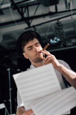 selective focus of handsome musician holding music book sheets and smoking cigar