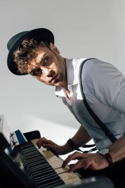 selective focus of serious musician in black hat playing piano