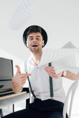 happy musician in black hat and white shirt throwing music book sheets