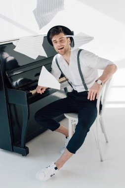 smiling musician in trendy clothing sitting by piano and throwing music book sheets